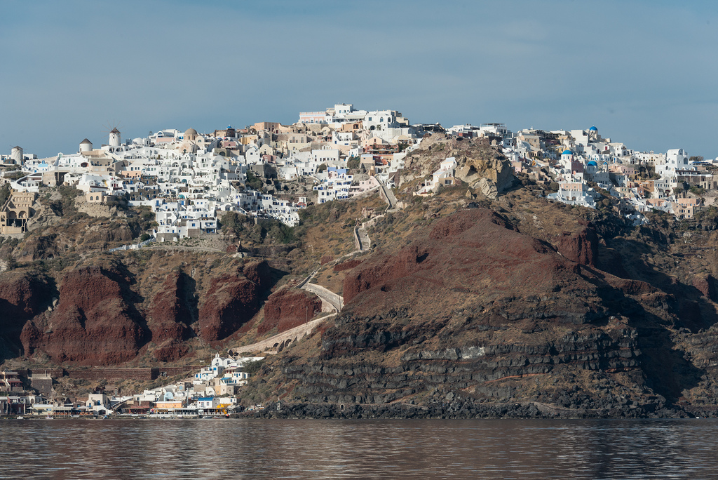 Fira, the capital of Thira (Santorini) as seen from the water. You can reach Fira by car on the back side of the rim, but if you want to get to it from the water, your best options are to ride a mule or take the cable car.