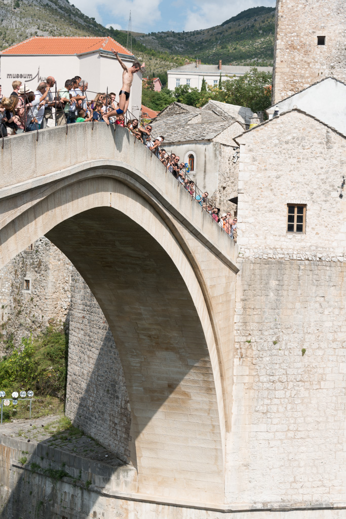 Bridge jumpers will throw themselves off the old bridge when their assistants have raised enough money from spectators.